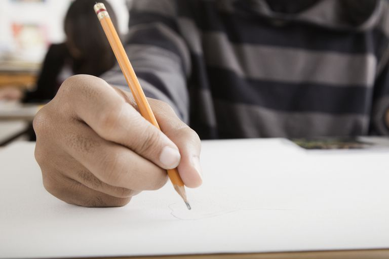 Student's hand writing with pencil