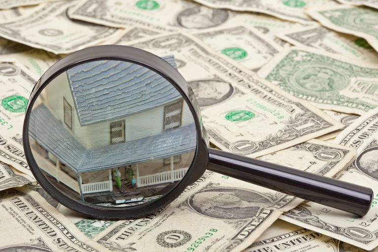 magnifying glass in front of house figurine on top of dollar bills