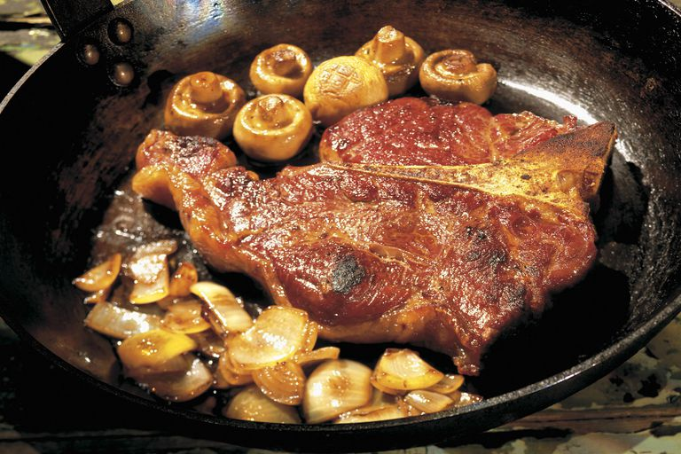 Steak cooking in a pan with mushrooms and onions