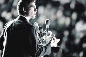 Man standing at podium, giving speech, crowd in background