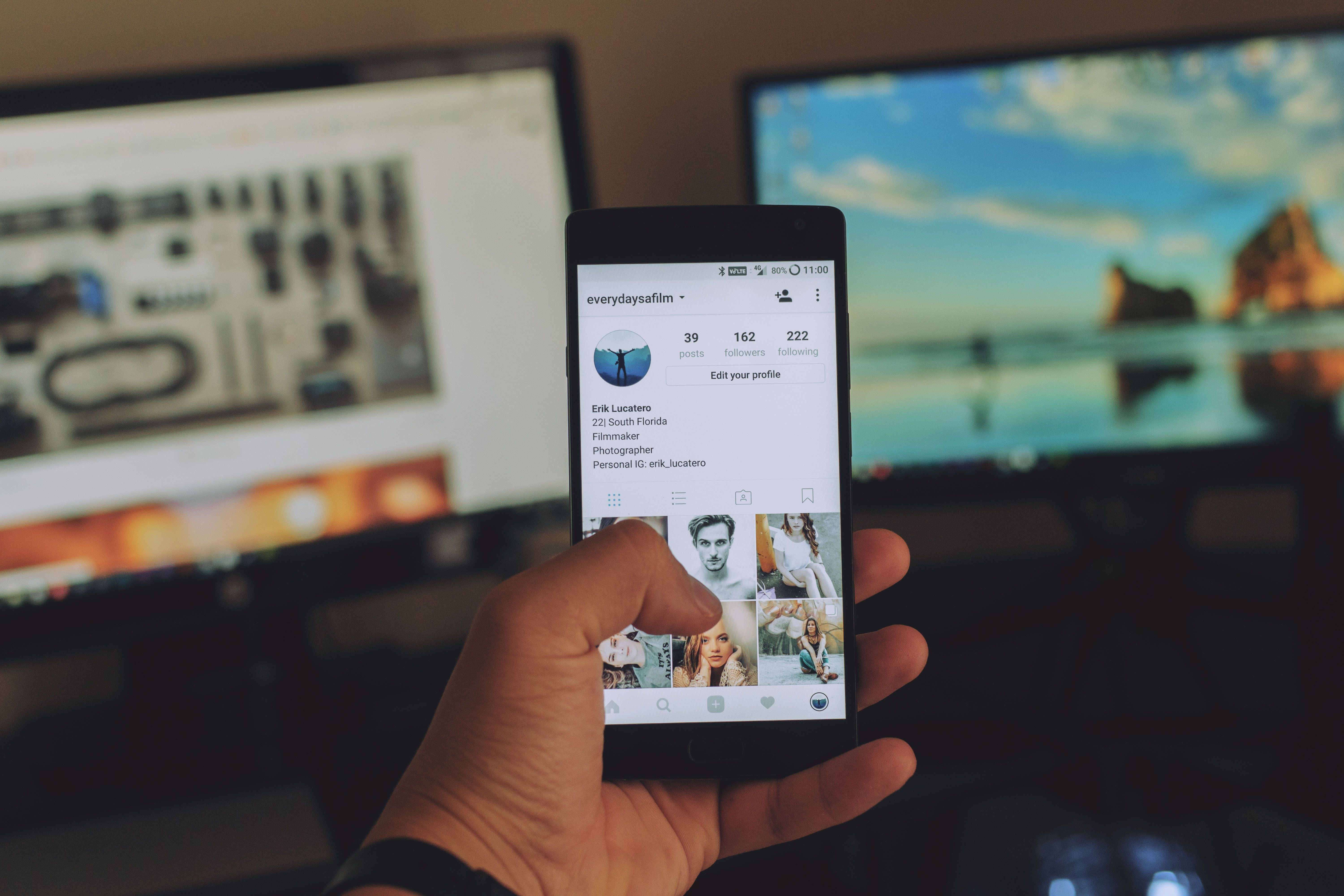 A picture of someone holding up a smartphone showing an Instagram profile.