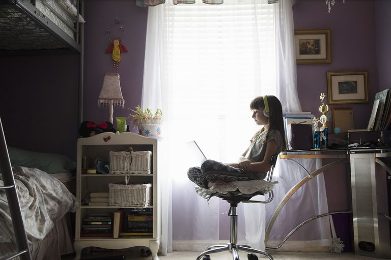Young girl studying through technology at home