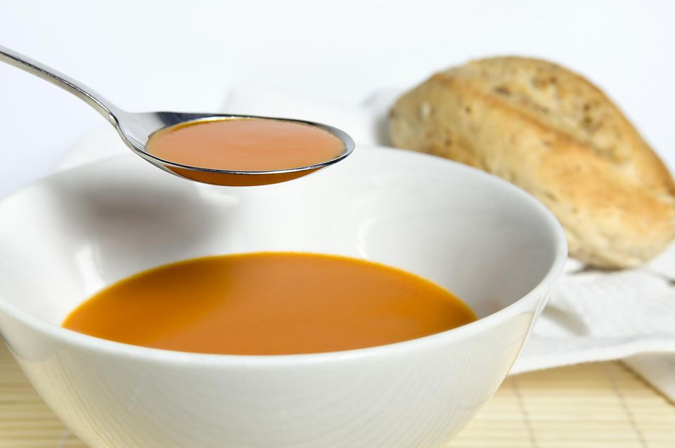 A spoonful of tomato soup from a bowl, and a roll