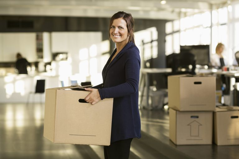 Woman moving boxes into her new office