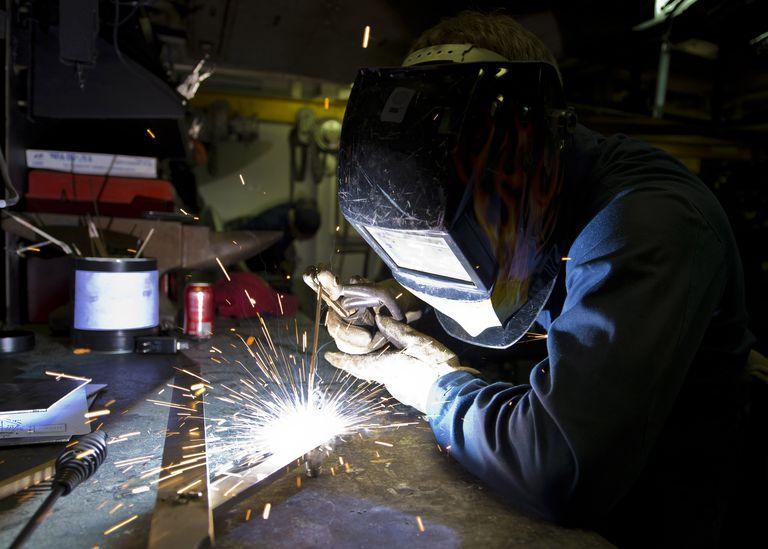 Hull Maintenance Technician strikes a welding rod.
