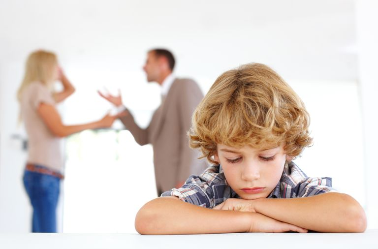Young boy listening to his parents fighting