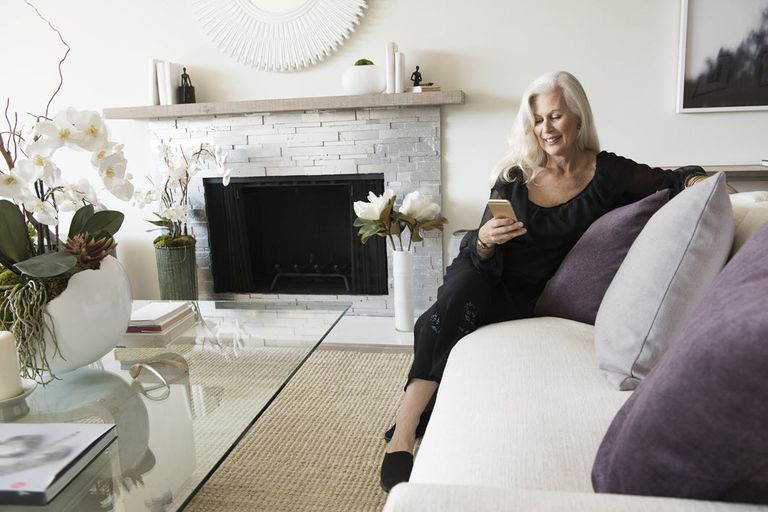 Woman sitting on a couch in a white room reading a book on her iPhone.
