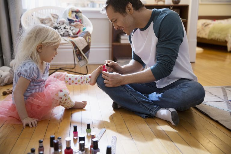 Father painting daughter toenails with fingernail polish