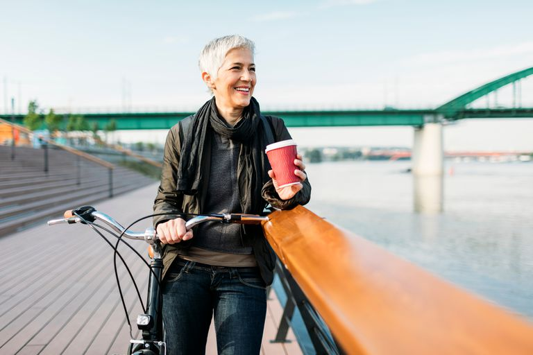 Woman on bike holding coffee