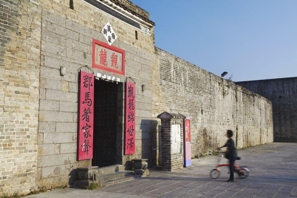 Woman entering San Wai walled village, Fanling, New Territories, Hong Kong, China