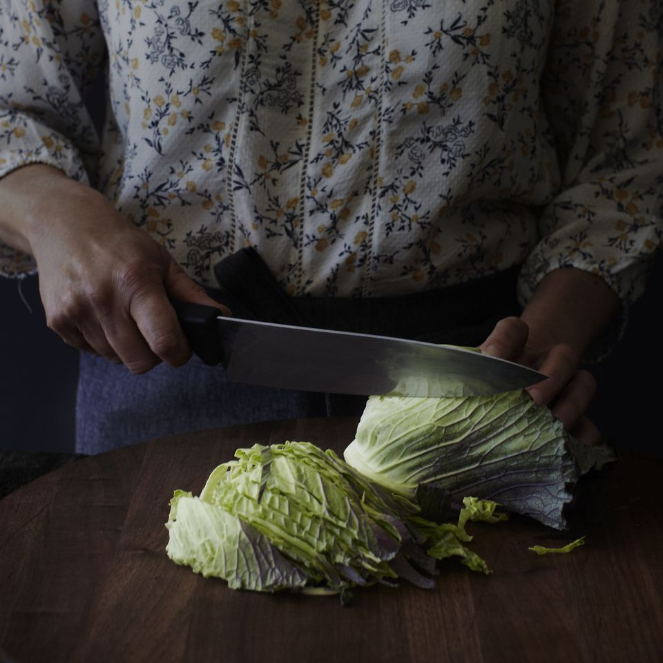 Cropped view of woman chopping cabbage with kitchen knife