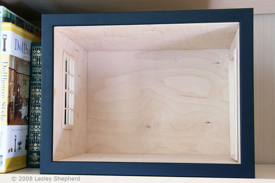 A simple picture frame encloses the front of a dolls house scale roombox which fits on a bookshelf.