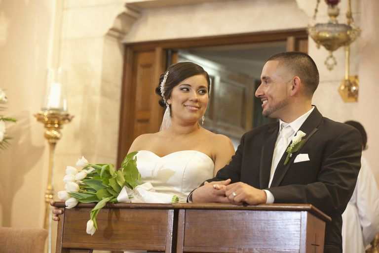 Hispanic bride and groom in wedding ceremony