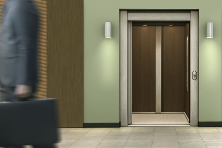 Businessman passing open elevator