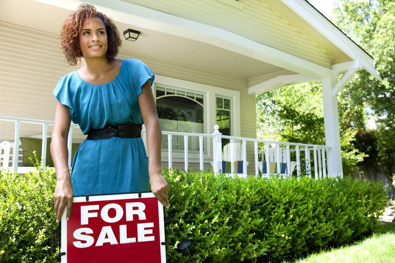 Young woman with a 'for sale' sign outside a house