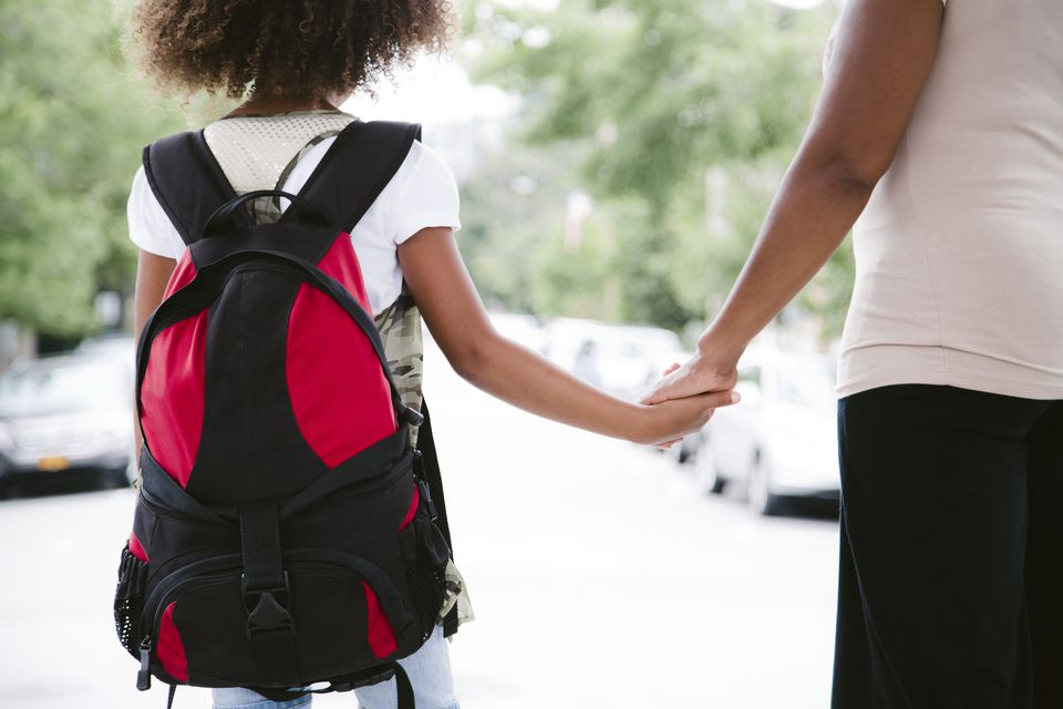 Girl with backpack walks to school with her mom.