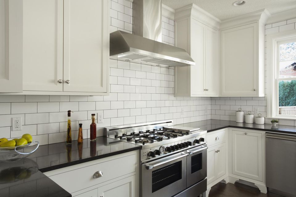 Custom designed kitchen with white cabinets and professional style stove.