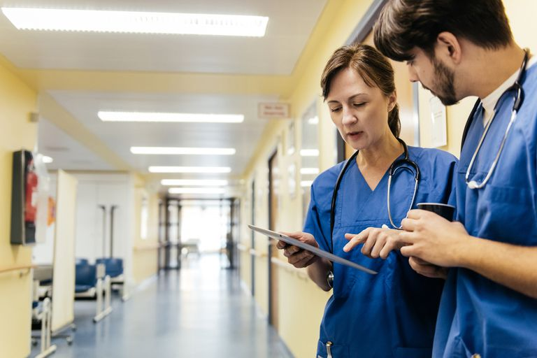 doctor and nurse talking and looking at digital tablet in hospital hallway