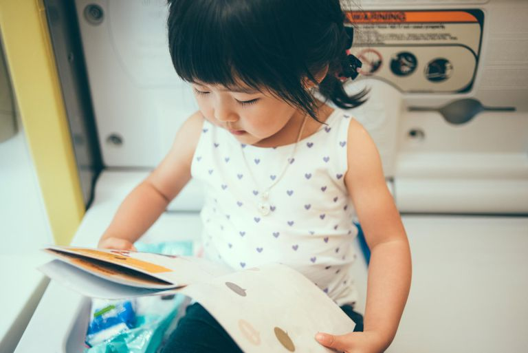 Toddler girl reading story book