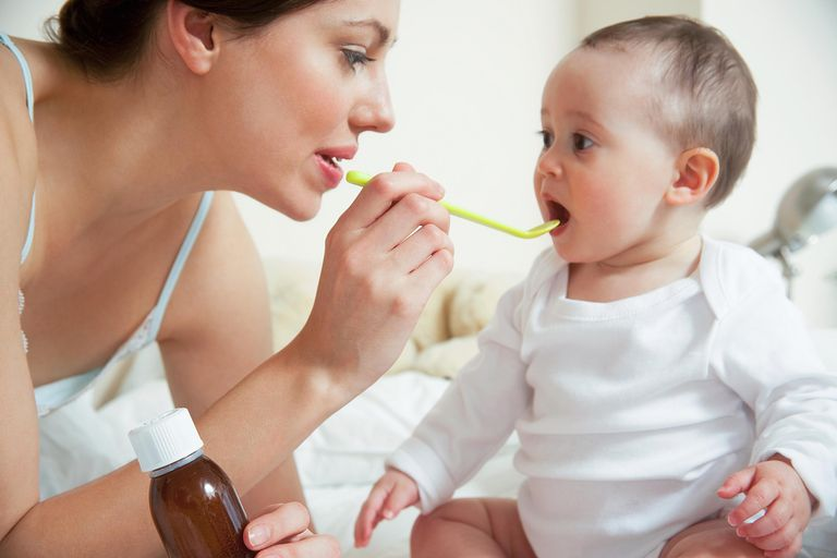 Mum administering syrup to baby in bedroom