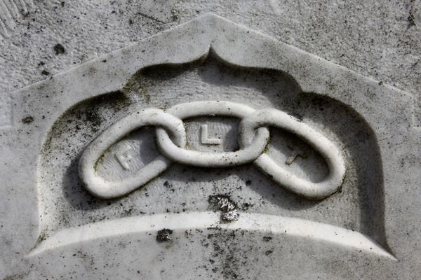 "Three-link chain with ""FLT"" on headstone"