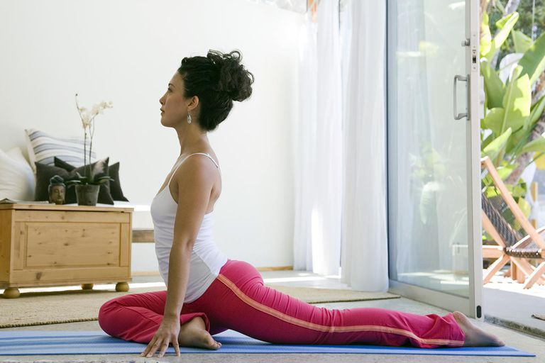 Woman sitting in yoga position at home, side view