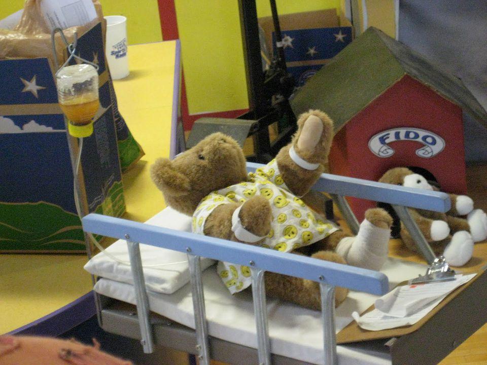 A teddy bear in a hospital bed with a honey IV