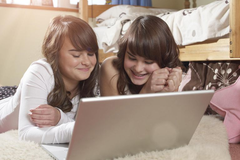 Female identical twins sharing a laptop.