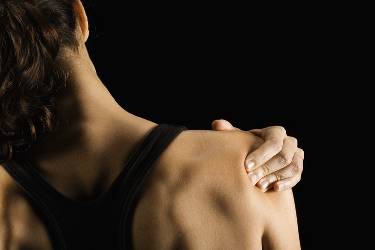 Woman rubbing shoulder, rear view