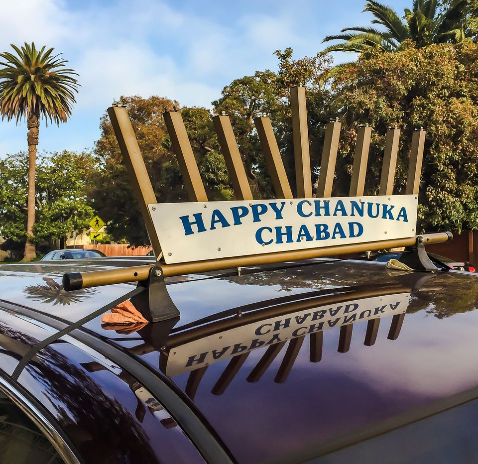 A menorah mounted on the top of a car driven by a Chabad volunteer on the seventh day of Hanukkah