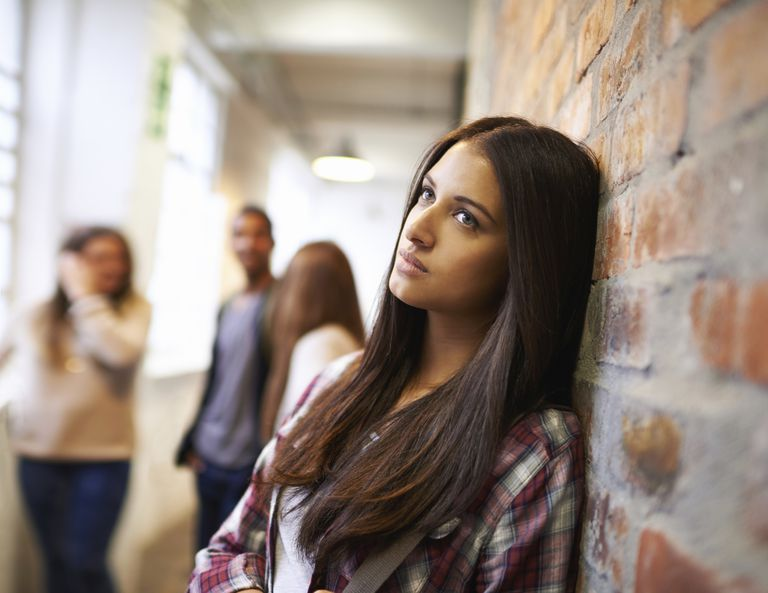 sad student leaning against wall