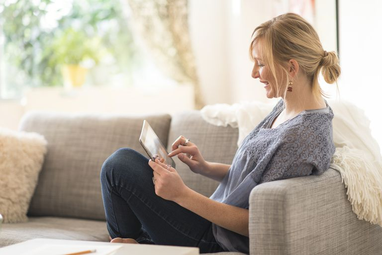 Woman sitting on sofa and using tablet pc