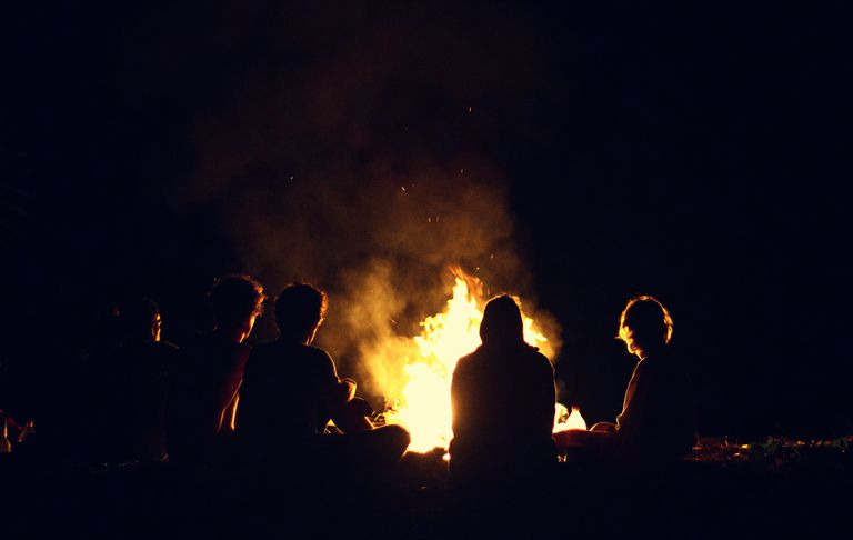 Friends by a campfire are an example of one important reason for the control of fire: human socialization.