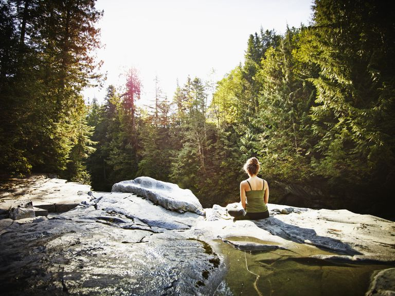 Woman meditating on rocks in the forest