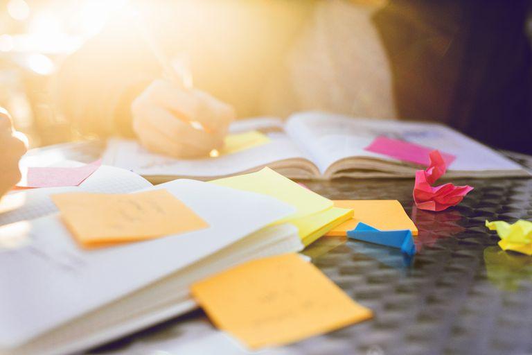 Teenage boy writing in book on table