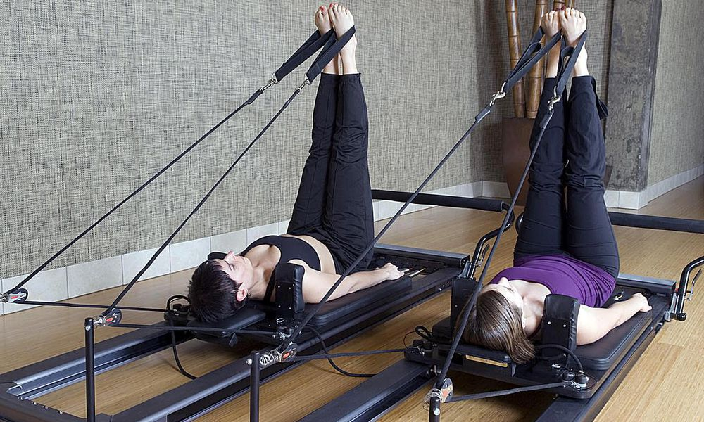 Two woman doing leg exercises on pilates reformer machines. Rear angle view with legs straight up. Click below for more in this series plus my other working out and staying fit images:
