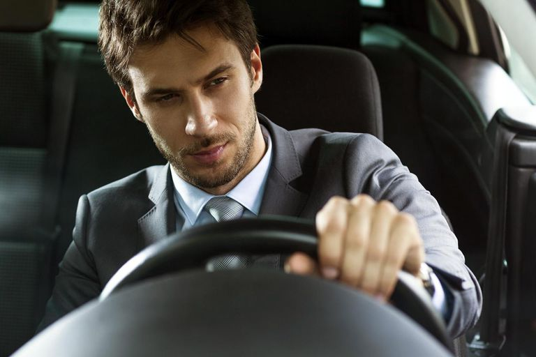 close up of a handsome young businessman driving car