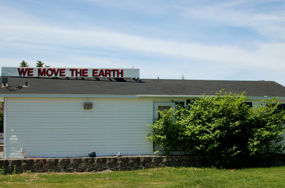 Image: ironic sign -- loam company has weeds in front of their establishment.