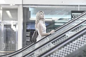 Woman going up an escalator