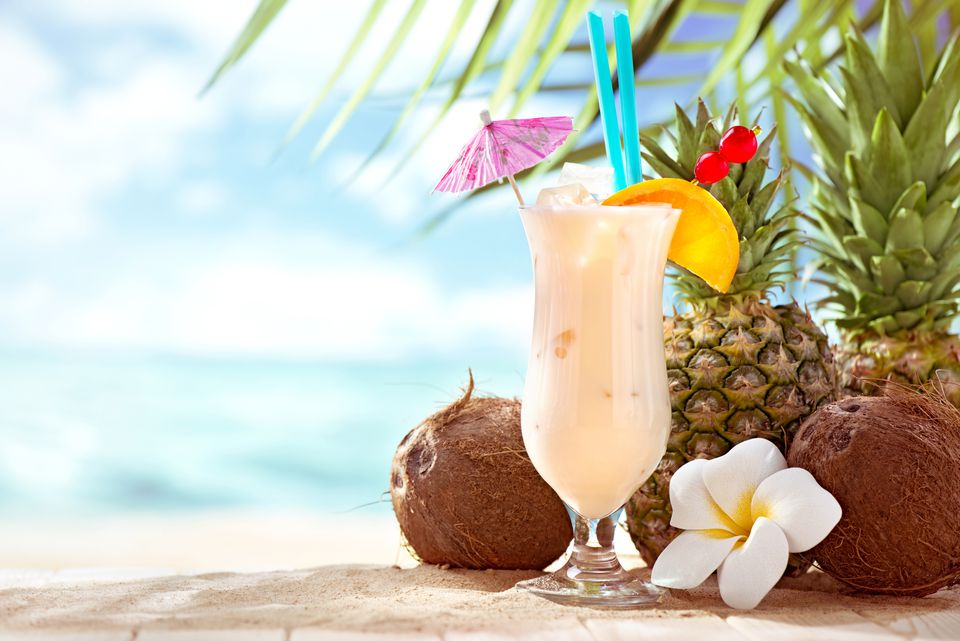 Pina Colada cocktail on the beach with coconuts