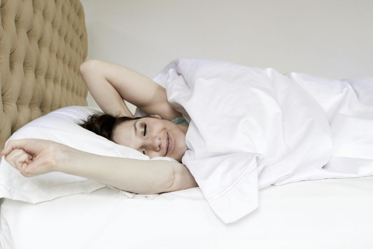 Woman waking and stretching in bed