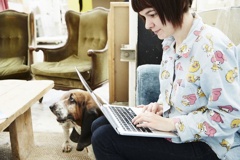 Young woman using laptop, dog in background