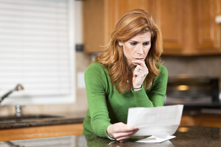 Concerned woman reading papers