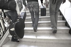 Three adults with instrument cases walking up stairs