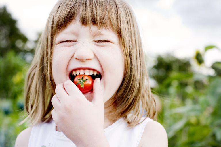 Girl biting cherry tomato, close up