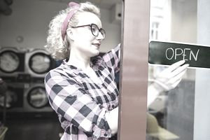 Female small business owner putting up open sign on laundrette door