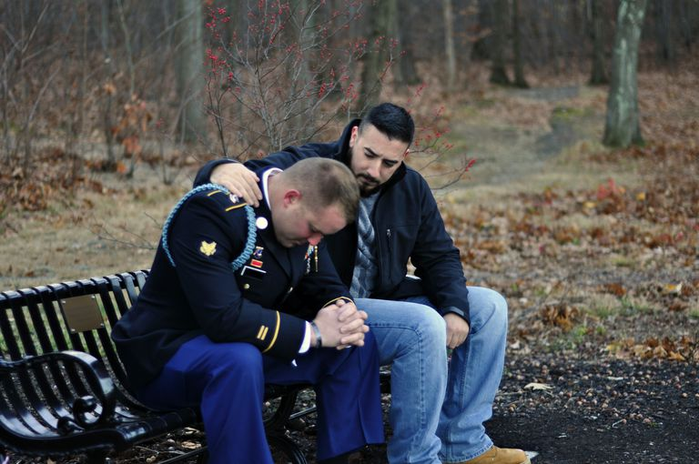 two men sitting on a park bench, one depressed and the other talking to and comforting him