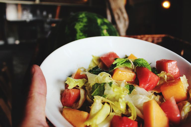 Cropped Image Of Hand Holding Bowl With Salad