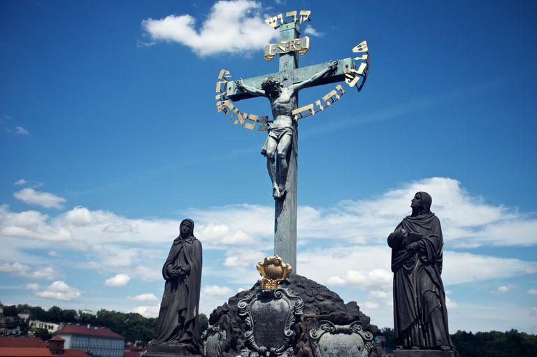 Ornate cross and statues in city