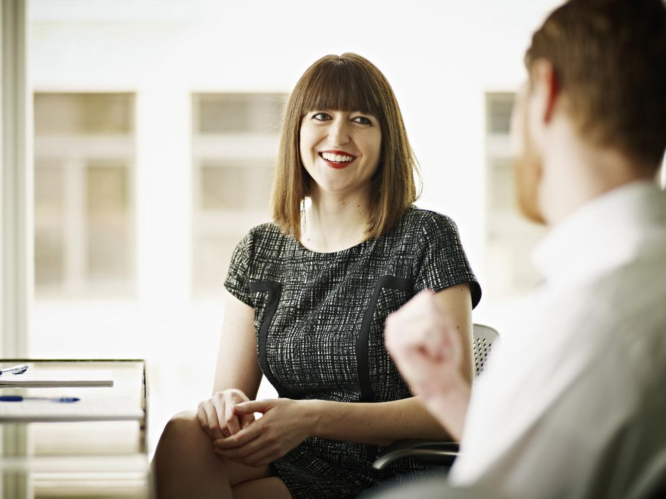 Businesswoman and businessman in discussion at office conference room table